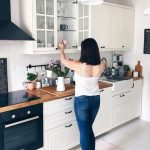 Glass front glass cabinets, wood worktop, white cupboards with black handles, wh...