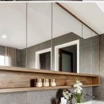 This modern ensuite bathroom features a large walk-in shower, a long white vanit...